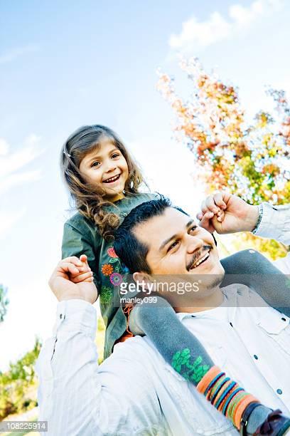 Niña sentada sobre los hombros de los padres