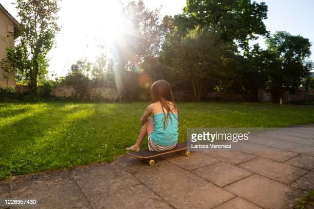 little girl sitting on her skateboard - larissa veronesi stock-fotos und bilder