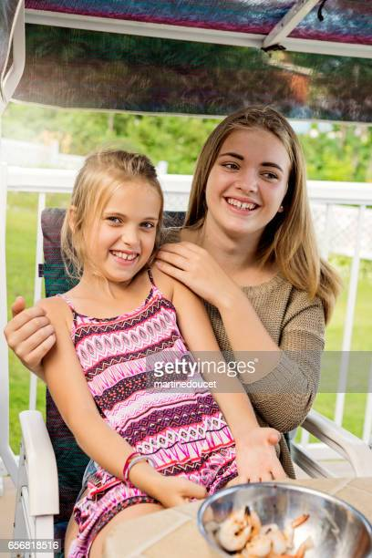 Little girl sitting on lap of sister at summer BBQ.
