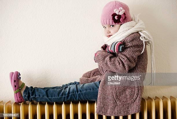 Little girl sitting on radiator