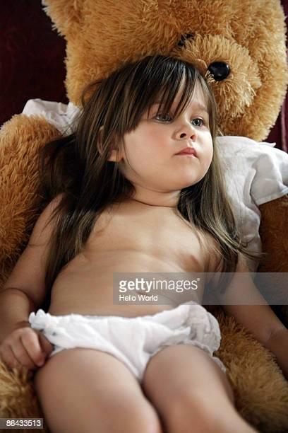little girl sitting on teddy bear