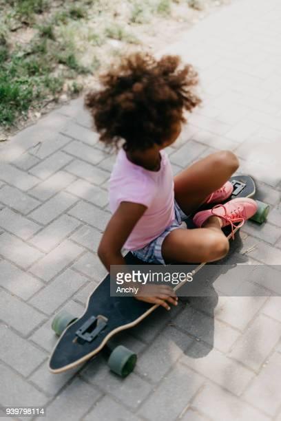 Little girl sitting on the longboard