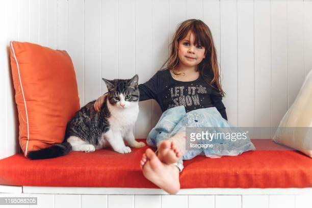 little girl sitting with her cat - cat family stock pictures, royalty-free photos & images