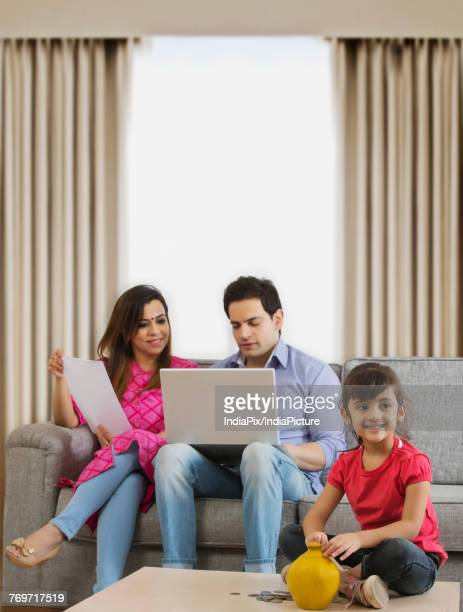 Little girl sitting with piggy bank and parents looking home finances
