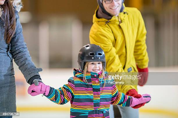 little girl skating with her parents - skating stock pictures, royalty-free photos & images