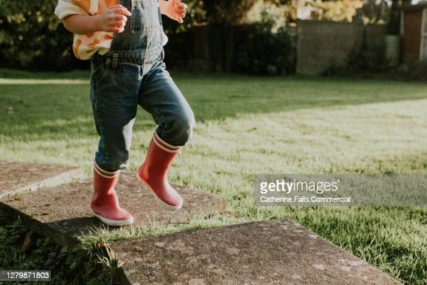 little girl skipping along paving stones in pink wellies - the way forward stock pictures, royalty-free photos & images