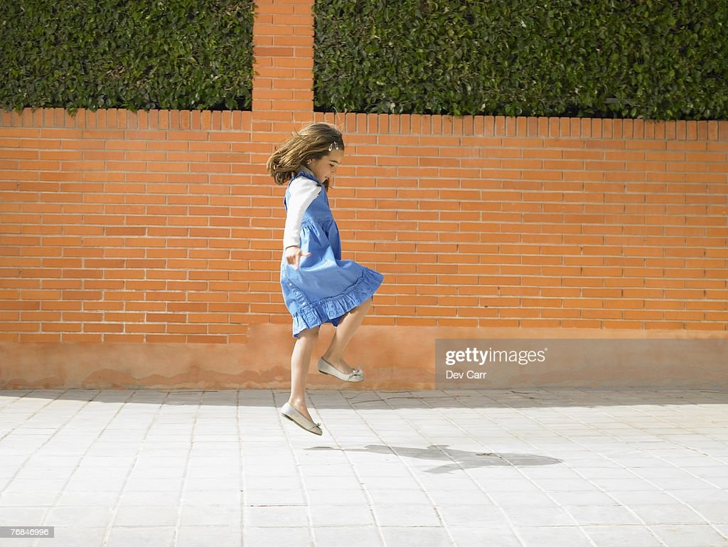 Little girl  (5-7) skipping down pavement, Alicante, Spain, : Stock Photo