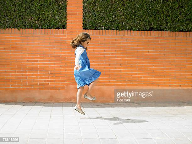 little girl  (5-7) skipping down pavement, alicante, spain, - skipping along stock photos and pictures