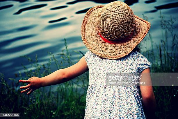 Little girl skipping stones at lake