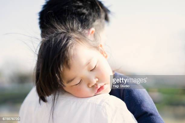 Little girl sleeping on the father's shoulder