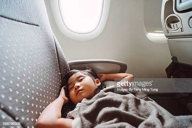 Little girl sleeping soundly in the airplane