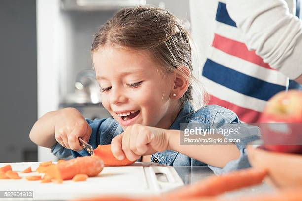 Little girl slicing carrots in kitchen