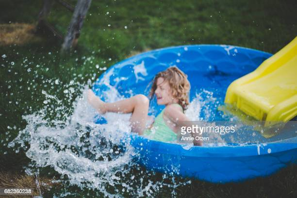 little girl sliding into kiddy pool - annie sprinkle stock pictures, royalty-free photos & images