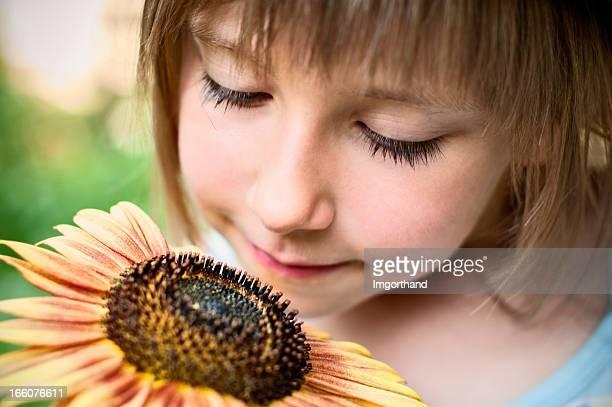 Kleines Mädchen riechen Blumen