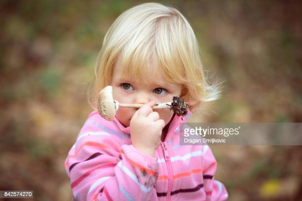 Little girl smelling parasol mushrooms