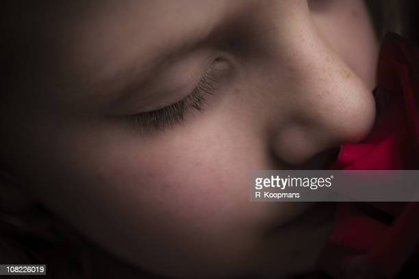 Kleines Mädchen riechen Rote Rose