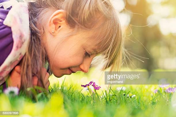 Kleines Mädchen riechen Blumen Frühling