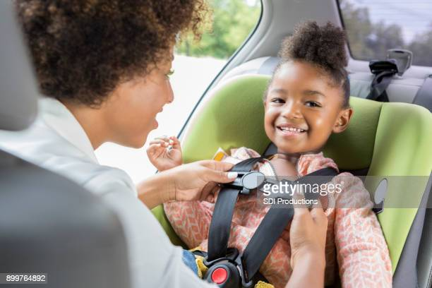 Little girl smiles as she is buckled into car seat