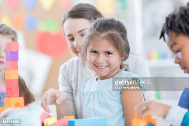 Little girl smiles for camera during kindergarten play time