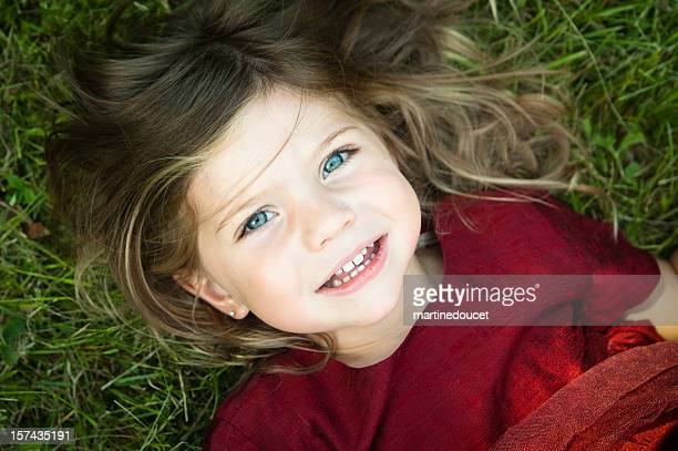 Little girl smiling and lying on grass.