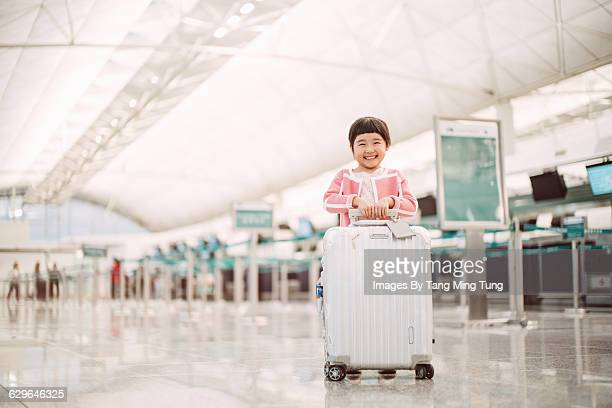 Little girl smiling at camera in airport