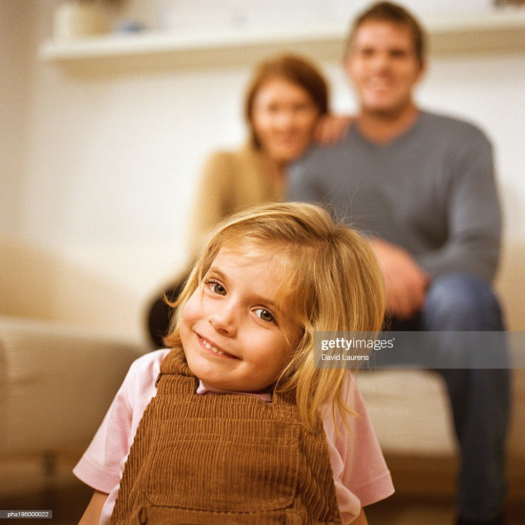 Little girl smiling at camera, parents behind her. : Stockfoto