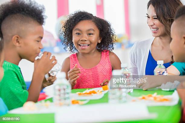 Little girl smiling at friend during snack time at daycare