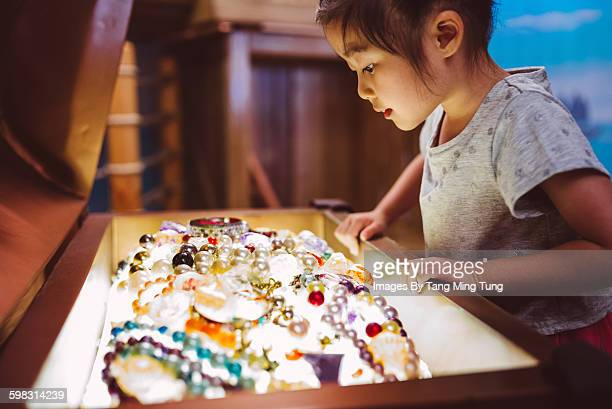 little girl smiling at opened toy treasure box