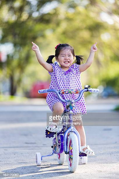 little girl smiling happily on her tricycle - hands free cycling stock pictures, royalty-free photos & images