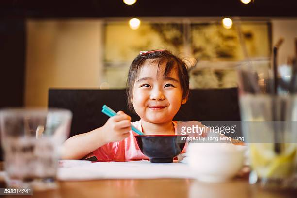 little girl smiling & having meals with chopstick