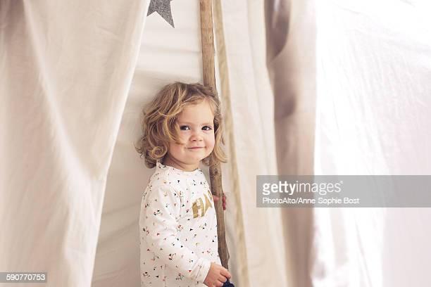 Little girl smiling in tent, portrait
