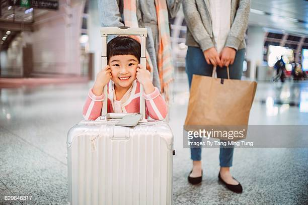 Little girl smiling joyfully at camera in airport