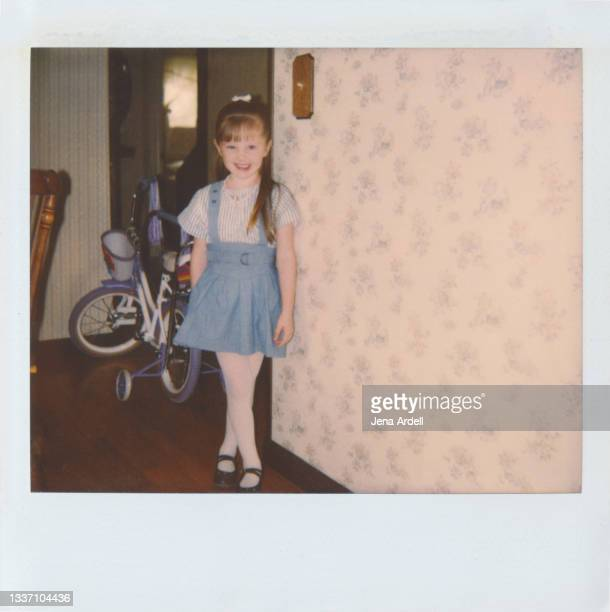 little girl smiling next to her birthday present: a bicycle with training wheels, vintage photograph 1980s kid - 1980 1989 stock pictures, royalty-free photos & images