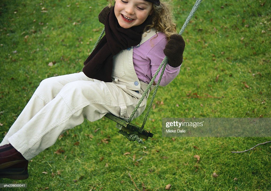 Little girl smiling on a swing. : Stock Photo