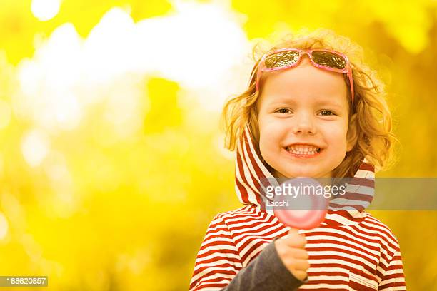 Little girl smiling with a lollipop on a yellow background