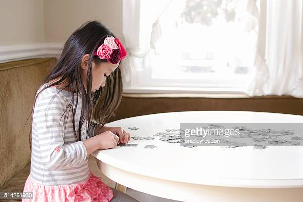 Little girl solving a jigsaw puzzle