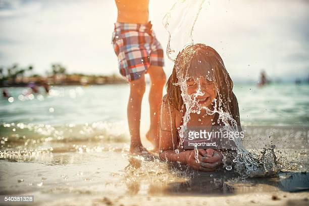 Little girl splashed with bucket of water