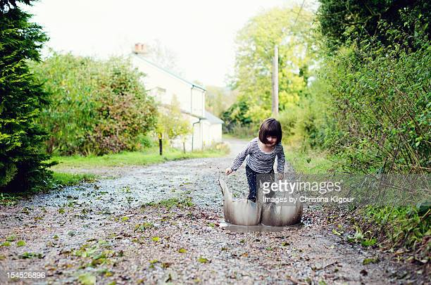Little Girl Splashing In A Muddy Puddle