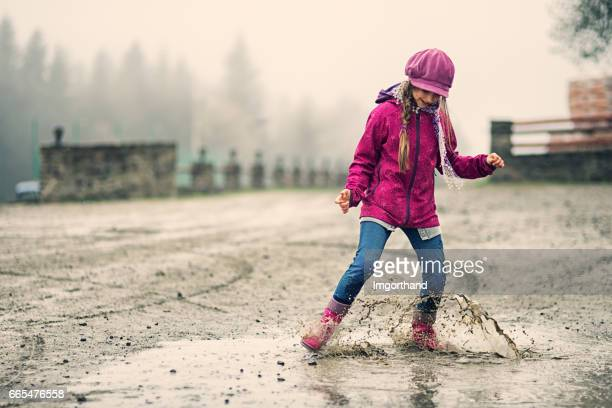 Little girl splashing in early spring puddle