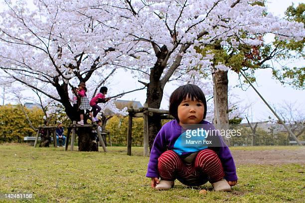 little girl squats to rest in middle of park - yonago stock photos and pictures