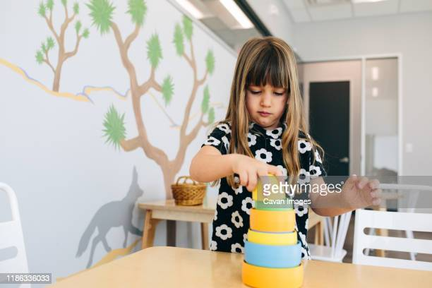 little girl stacks cylinders in an educational facility - calabasas stock pictures, royalty-free photos & images