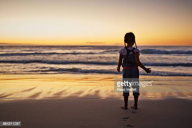 Little girl standing alone on beach, at sunset