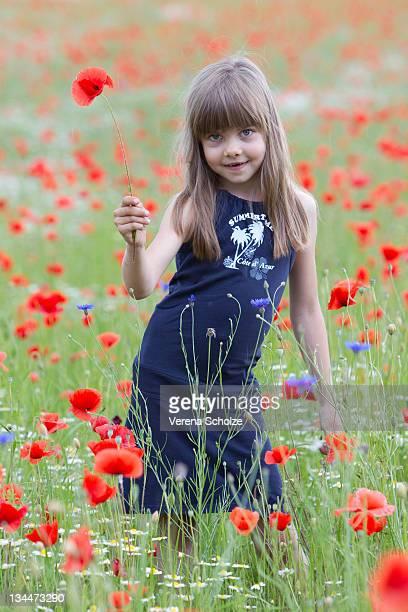 Little girl standing in a poppy field