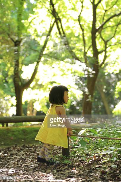 Little girl standing in forest
