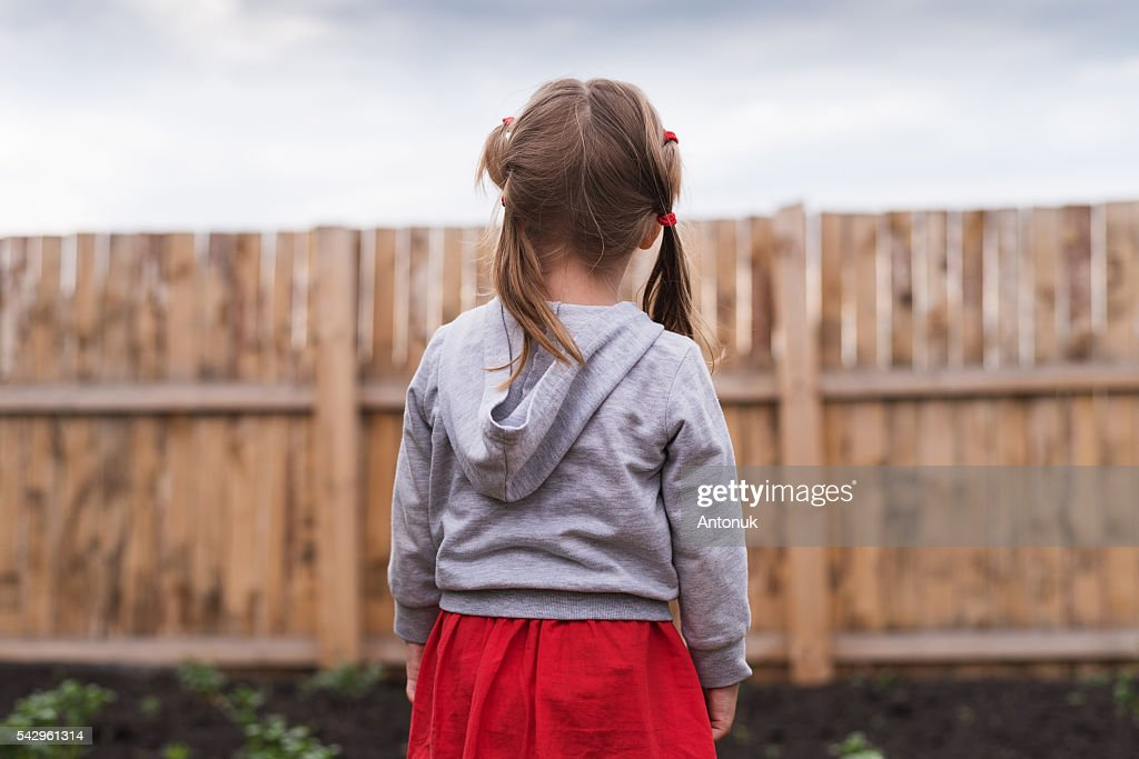 Little girl standing in front of a fence : Stock Photo