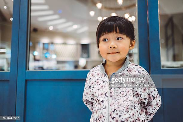 Little girl standing in front of blue door smiling