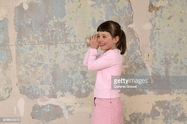 Little Girl Standing in Front of Damaged Wall, Holding Tin Can Phone
