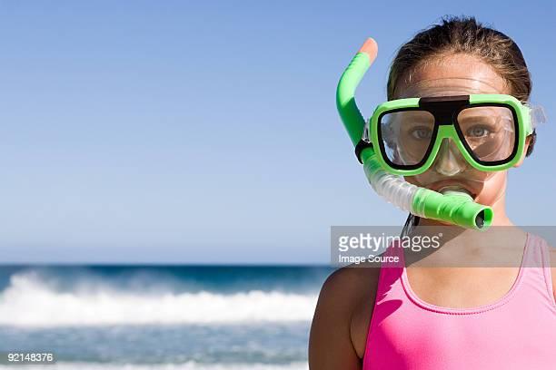Bambina in piedi di fronte oceano indossando maschera per lo snorkeling