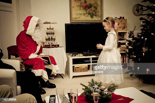 Little girl standing in front of Santa