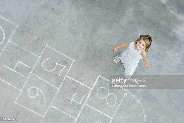 Little girl standing next to hopscotch squares, smiling up at camera, high angle view